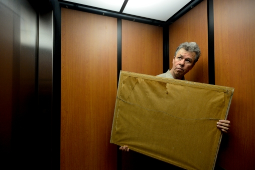 Dr. Gregory Jaramillo carries artwork while riding in an elevator to the first floor at Salud Family Health Center in Longmont on Wednesday. Go to timescall.com for more photos. Matthew Jonas / Staff Photographer April 1, 2015